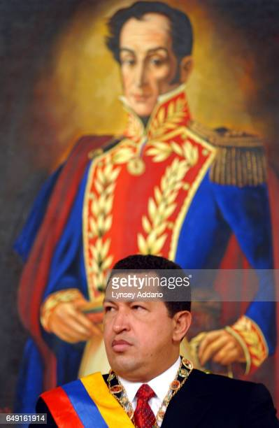 Venezuelan President Hugo Chavez sits below a painting of his hero, South American military and political leader Simon Bolivar, during a press...