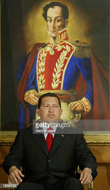 Venezuelan President Hugo Chavez sits under a painting of the country's liberator Simon Bolivar before swearing in a new board of directors for state...
