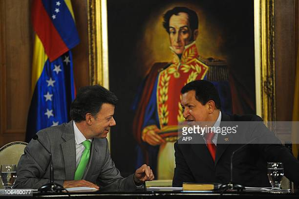 Venezuelan President Hugo Chavez speaks with his Colombian counterpart Juan Manuel Santos in front of a portrait of South American independence hero...