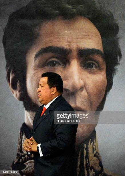 Venezuelan President Hugo Chavez walks in front of a picture showing the possible face of Liberator Simon Bolivar a digital rendering from genetic...