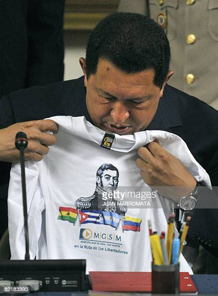 Venezuelan President Hugo Chavez watches a jersey with the portrait of Argentine national hero General Jose de San Martin during a ceremony at San...