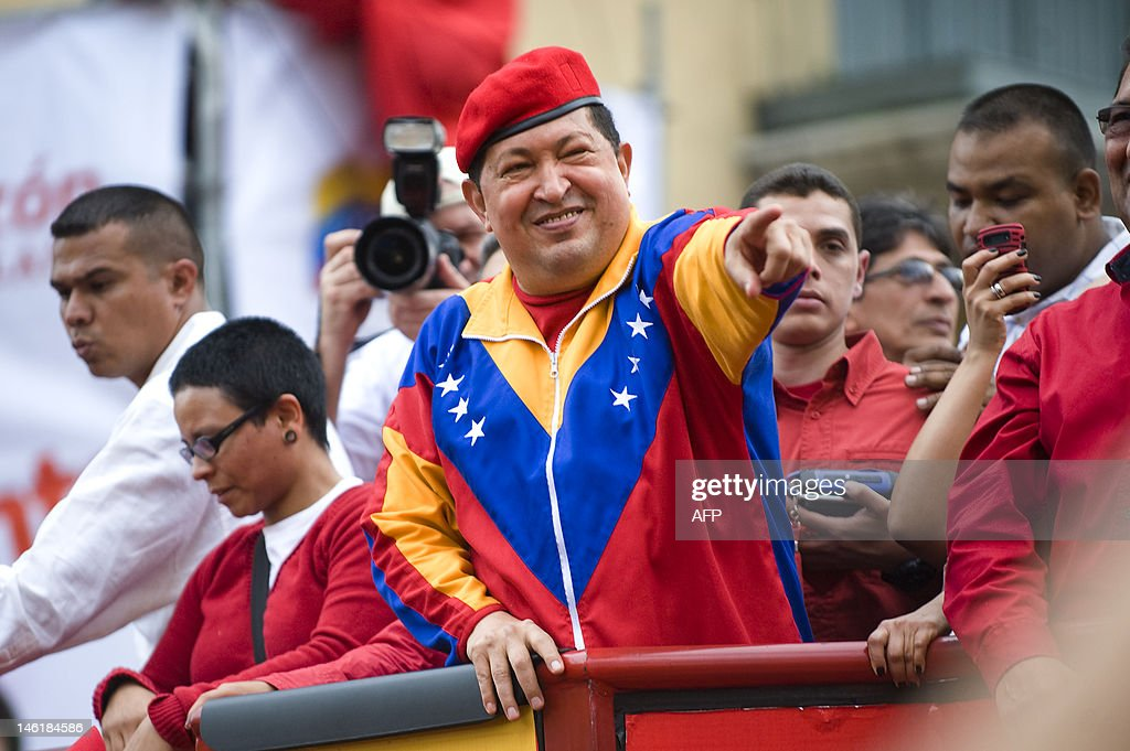 Venezuelan President Hugo Chavez (C) waves to supporters during a caravan before registering his candidacy in the National Electoral Center for the upcoming presidential election, in Caracas on June 11, 2012. Thousands of followers took to the streets of Caracas supporting his candidacy. AFP PHOTO/Leo RAMIREZ