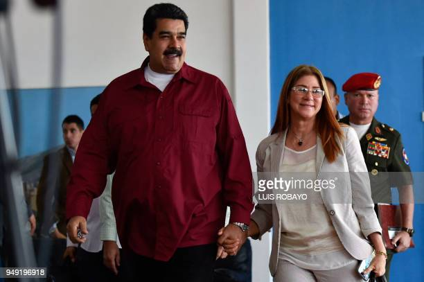 Venezuelan President Nicolas Maduro accompanied by first lady Cilia Flores arrives to deliver a press conference at the Simon Bolivar International...