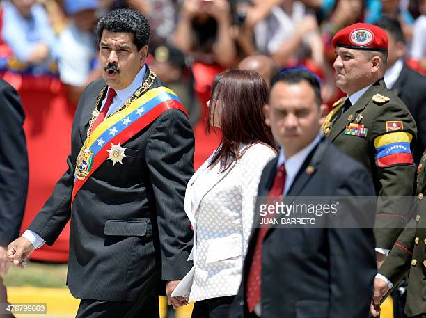 Venezuelan president Nicolas Maduro and firts lady Cilia Flores greets supporters before a military parade in Caracas on March 5 2014 The Venezuelan...