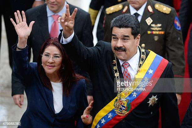 Venezuelan President Nicolas Maduro and his wife Cilia Flores wave upon their arrival at the National Assembly for a session commemorating...