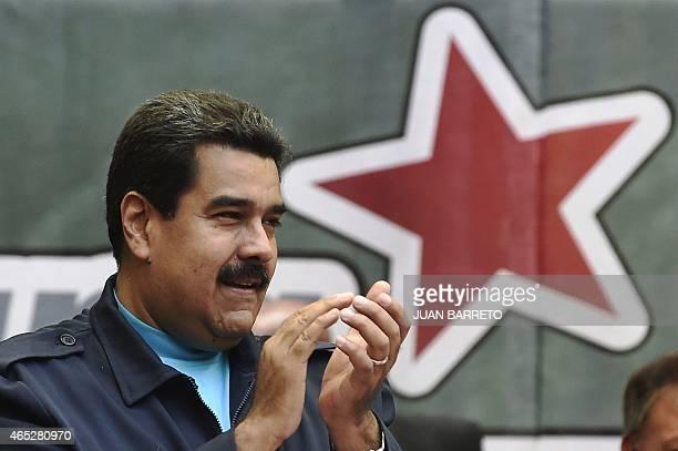 Venezuelan President Nicolas Maduro applauds during a ceremony commemorating the second anniversary of former Venezuelan president Hugo Chavez's...