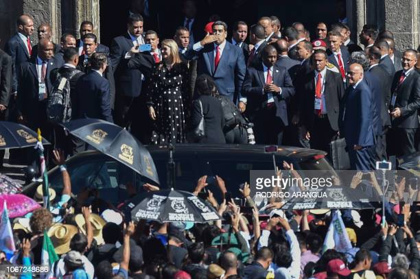 Venezuelan President Nicolas Maduro blows a kiss next to his wife Cilia Flores outside the National Palace in Mexico City on December 1 as they...