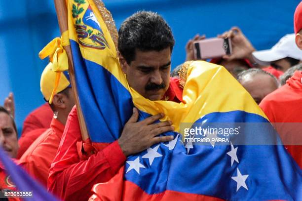 TOPSHOT Venezuelan President Nicolas Maduro holds a national flag during the closing of the campaign to elect a Constituent Assembly that would...