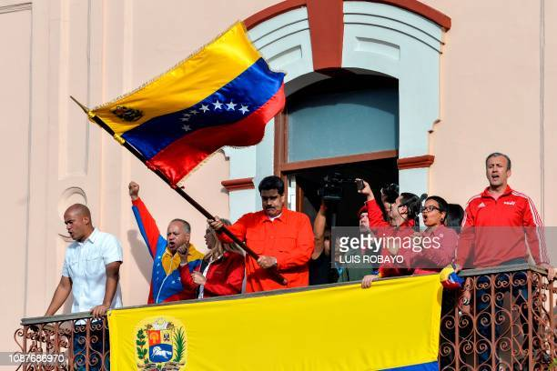 TOPSHOT Venezuelan President Nicolas Maduro holds a national flag while speaking to a crowd of supporters at the Miraflores Palace flanked by his...