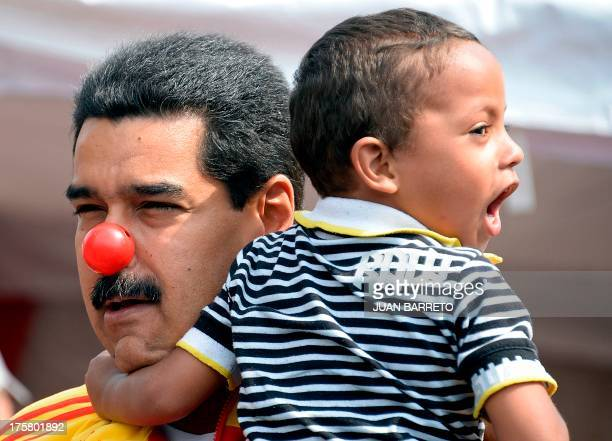 Venezuelan President Nicolas Maduro is seen with a clown's nose as he holds a boy during an event to promote a public disarmament program at '23 de...