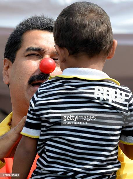 Venezuelan President Nicolas Maduro is seen with a clown's nose as he jokes with a boy during an event to promote a public disarmament program at '23...