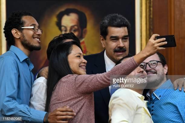 Venezuelan President Nicolas Maduro poses for a selfie with Venezuelan journalists during the Simon Bolivar national journalism award ceremony at...