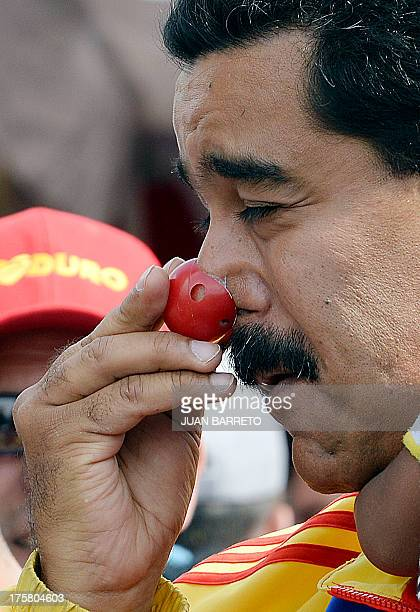 Venezuelan President Nicolas Maduro puts on a clown's nose as he holds a boy during an event to promote a public disarmament program at '23 de Enero'...