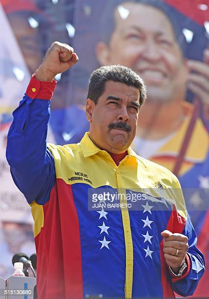 Venezuelan President Nicolas Maduro raises his clenched fist during a demonstration against the United States' decision to renew sanctions on several...