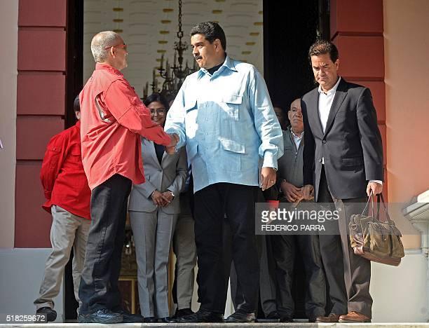 Venezuelan President Nicolas Maduro shakes hands with thecountry's ELN leftwing guerrilla Eliecer Herlinton Chamorro Acosta aka Antonio Garcia next...