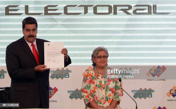 Venezuelan President Nicolas Maduro shows the document issued by the National Electoral Council that proclaims him as reelected President for the...