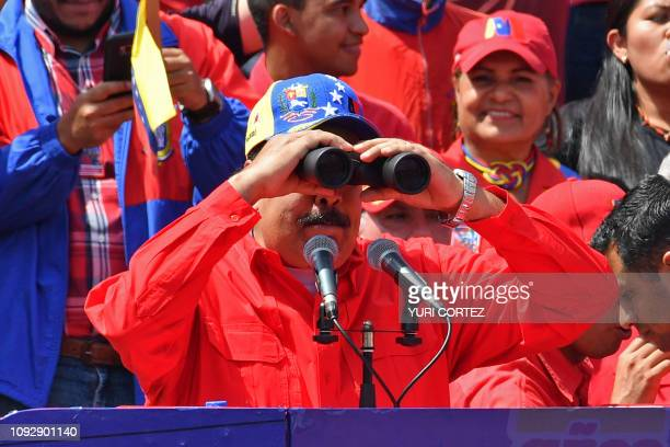 Venezuelan President Nicolas Maduro uses binoculares during a gathering to mark the 20th anniversary of the rise of power of the late Hugo Chavez the...
