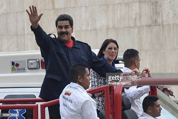 Venezuelan President Nicolas Maduro waves as he arrives with his wife Cilia Flores to the celebrations for the fifth anniversary of the Bolivarian...