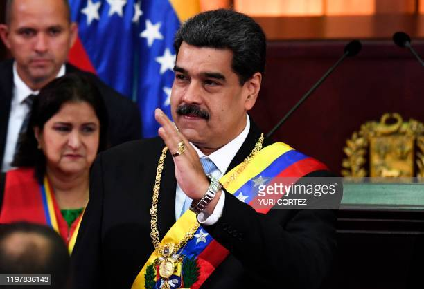 Venezuelan President Nicolas Maduro waves during the opening ceremony of the judicial year at the Supreme Court of Justice in Caracas on January 31...