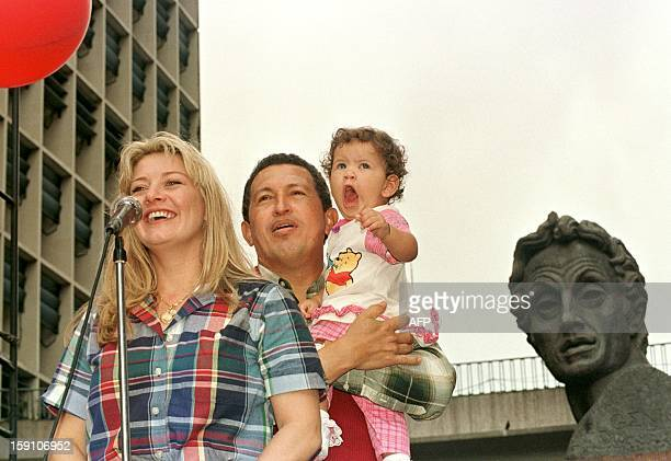 Venezuelan presidential candidate Hugo Chavez Frias attends with his wife Marisabel and his daughter Rosaines a political meeting of his supporters...