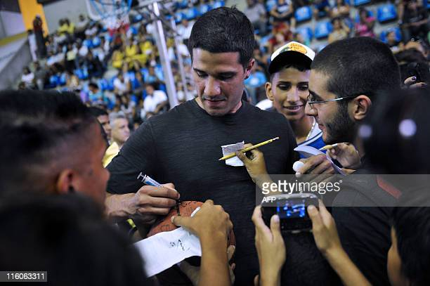 Venezuelan professional NBA player Greivis Vasquez signs autographs during a special workshop for young Venezuelan basketball players in Caracas on...