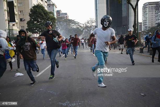 Venezuelan protesters flee while chased by Venezuelan National Guard troops on March 5 2014 in Caracas Venezuela Clashes between protesters and...