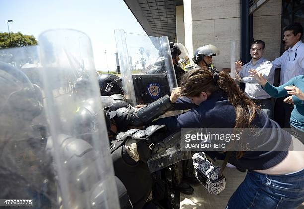 Venezuelan public health workers scuffle with riot police during a protest in Caracas on March 10 2014 At least 20 people have died and 300 others...