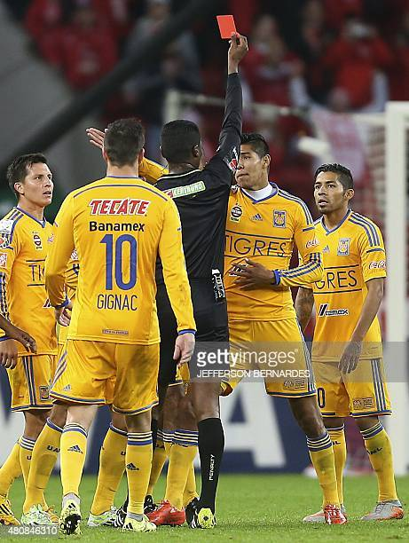 Venezuelan refree Jose Argote shows the red card to Hugo Ayala of Mexico's Tigres during their Libertadores Cup semifinal first leg football match at...