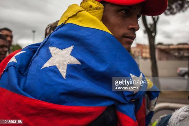 Venezuelan refugee wears a jacket of the Venezuelan national flag at an informal refugee camp called 'El Bosque' on October 2 2018 in Bogota Colombia...