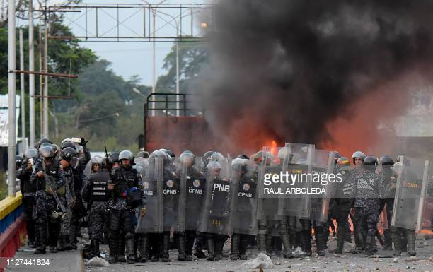 Venezuelan security forces stand in front of a truck which was burnt during the weekend when trying to enter the country with humanitarian aid during...