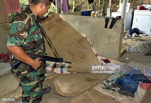Venezuelan soldier checks the belongings of alleged Colombian paramilitary members after their arrest in Daktari farm east of Caracas 09 May 2004...