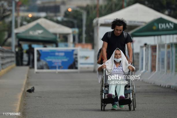 Venezuelan Steve Oliveros pushes his mother Alba de Oliveros' wheelchair back to Colombia after failing to cross the Simon Bolivar International...