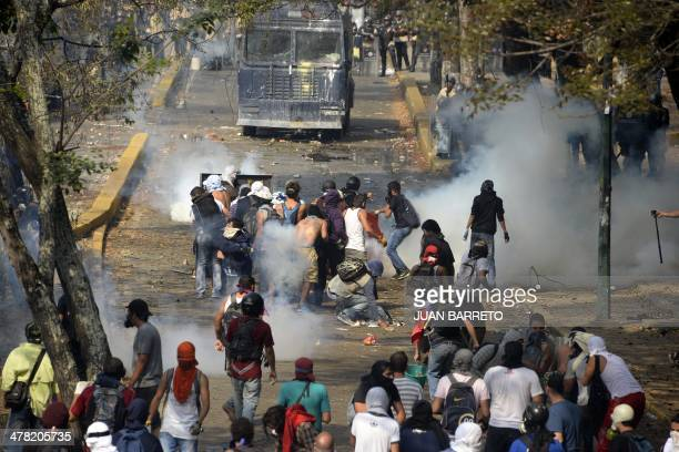Venezuelan students clash with riot police during a protest against the government of President Nicolas Maduro in Caracas on March 12 2014 A young...