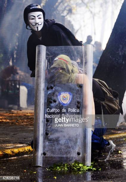Venezuelan students protect themselves with a shield of riot policemen during a protest against the government of President Nicolas Maduro in Caracas...