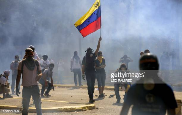 Venezuelan students walk amid tear gas shot by riot police during a protest against the government of President Nicolas Maduro in Caracas on March 12...