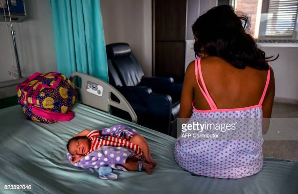 A Venezuelan teenager who migrated to Colombia with a friend three years ago fleeing from her parents violence sits next to her newborn Juan David at...