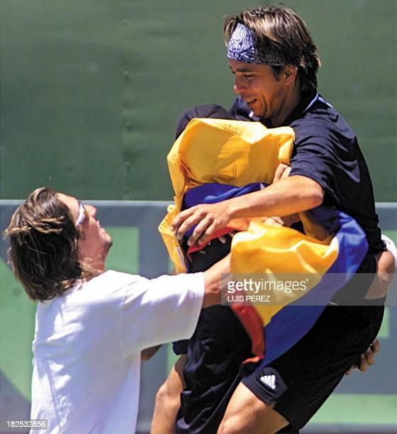 Venezuelan tennis player Jimy Szymanski celebrates his doubles team victory with team captain Victor Perez after a Davis Cup match against Guatemalan...