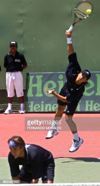 Venezuelan tennis player Jose de Armas performs a smash while his doubles teammate Jimy Szymanski stays close to the net during a Davis Cup match...