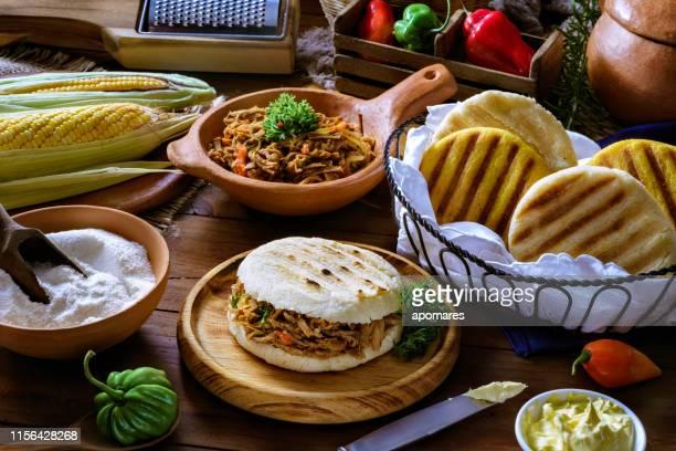 comida tradicional venezolana, arepa con carne rallada. ingredientes sobre una mesa en una cocina rústica. - caracas fotografías e imágenes de stock