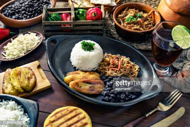 venezuelan traditional food, pabellon criollo with arepas, casabe and papelon with lemon drink - latin american culture stock pictures, royalty-free photos & images