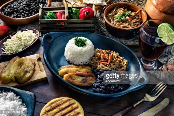 venezuelan traditional food, pabellon criollo with arepas, casabe and papelon with lemon drink - caracas fotografías e imágenes de stock