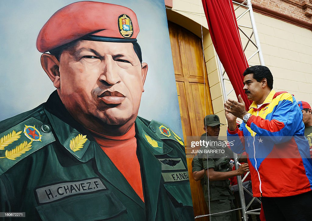 Venezuelan Vice President Nicolas Maduro (R) looks at a portrait of Venezuelan President Hugo Chavez during the conmemoration of the 1992 failed coup led by Chavez, who was an army lieutenant colonel, against then president Carlos Andres Perez, in Caracas, on February 4, 2013. Ailing President Hugo Chavez, who had cancer surgery in December, is doing much better and recovering, Cuban leader Fidel Castro said in remarks published Monday. AFP PHOTO/Juan BARRETO