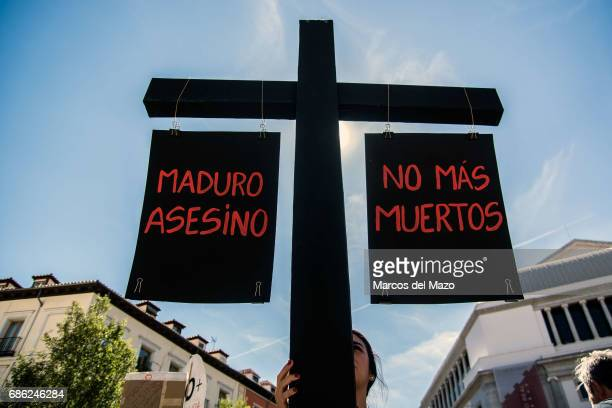 Venezuelan woman carrying a cross that reads Maduro murderer No more deaths during a demonstration to denounce that there is no respect for human...