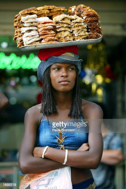 Venezuelan woman selling local food watches as supporters of Venezuelan President Hugo Chavez march through an antiChavez neighborhood December 19...