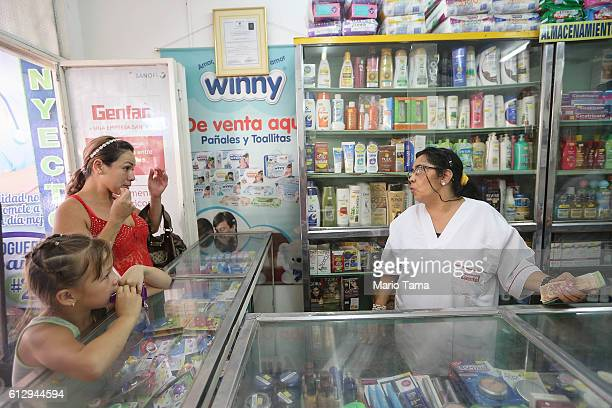 Venezuelan woman waits to purchase items from a pharmacy located near the international border bridge between Venezuela and Colombia on October 5...