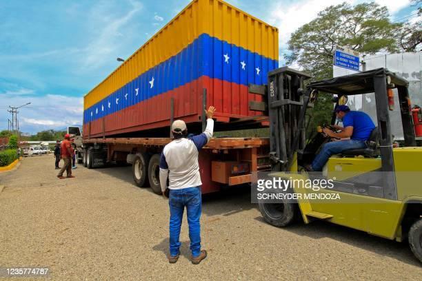 Venezuelan workers move a container on the Francisco de Paula Santander International Bridge that links Cucuta, Colombia, and Urena, Tachira state,...