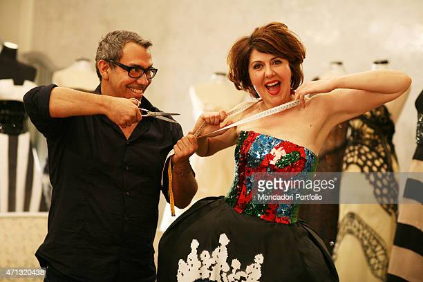 Venezuelanborn Italian art director at Maison Gattinoni Guillermo Mariotto joking with a tapemeasure around the neck of Italian actress Emanuela...