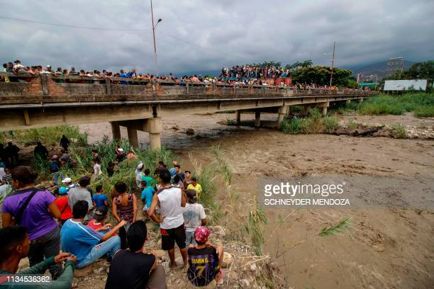 Venezuelans cross the blocked Simon Bolivar international bridge in Cucuta Colombia in the border with Venezuela as others watch from the bank of the...