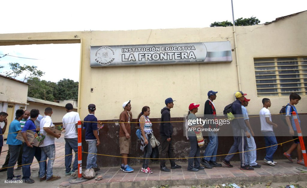 Venezuelans line up to get food at the Casa de Paso Divina Providencia refuge in Cucuta, Colombia on July 31, 2017. after crossed the Simon Bolivar international bridge from San Antonio del Tachira, Venezuela towards Cucuta , who must show the immigration card and the Venezuelan citizenship card to be able to access this assistance, by different companies and communities in the country /