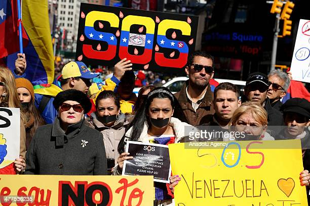 Venezuelans living in the United States attend a rally to draw attention to the latest situations held in Venezuela at the Times Square in New York...